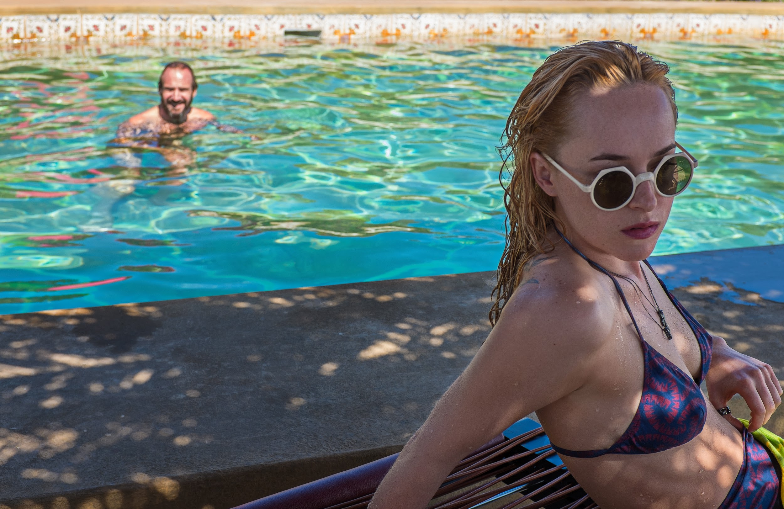 "Ralph Fiennes as ""Harry Hawkes"" and Dakota Johnson as ""Penelope Lanier"" in A BIGGER SPLASH. Photo courtesy of Fox Searchlight Pictures. © 2015 Twentieth Century Fox Film Corporation All Rights Reserved"